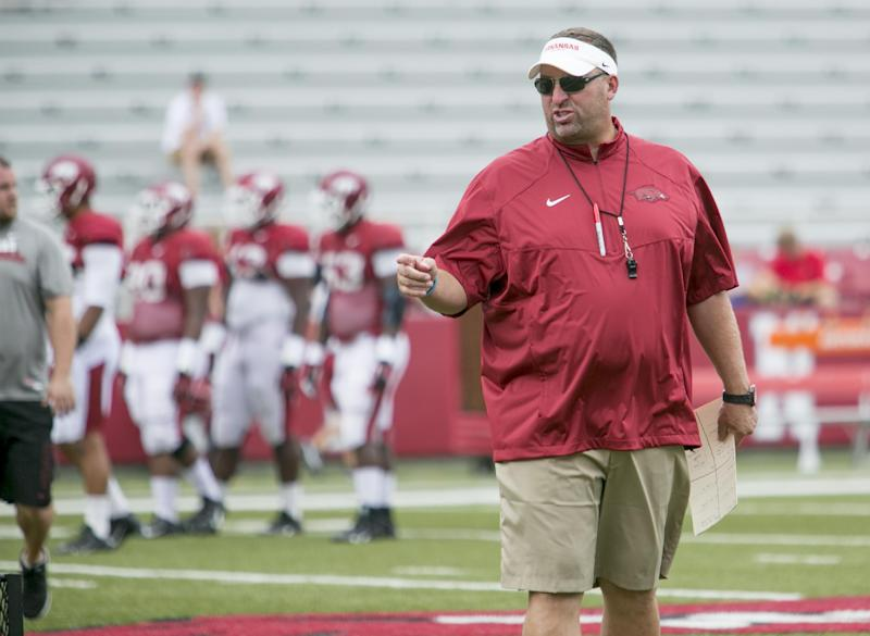 Arkansas head coach Bret Bielema gives instruction to a group of offensive players during a preseason NCAA college football practice at Donald W. Reynolds Razorback Stadium in Fayetteville, Ark., Saturday, Aug. 16, 2014