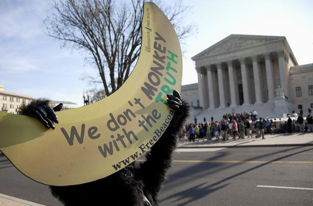 Protesters, including a man in a monkey suit, gather at the Supreme Court as the court concludes three days of hearing arguments on the constitutionality of President Barack Obama's health care overhaul.
