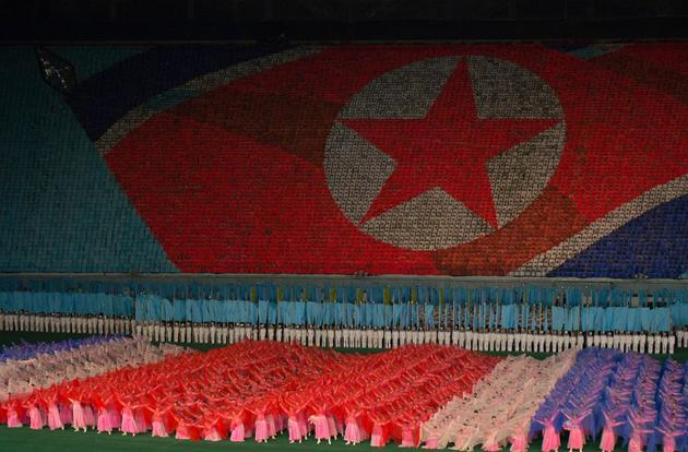 Students and dancers perform at the Arirang Mass Games in Pyongyang, the capital city of North Korea. The background mosaic is made up of children holding large books opened to a certain color to create the image. 100,000 performers are said to participate in the show.