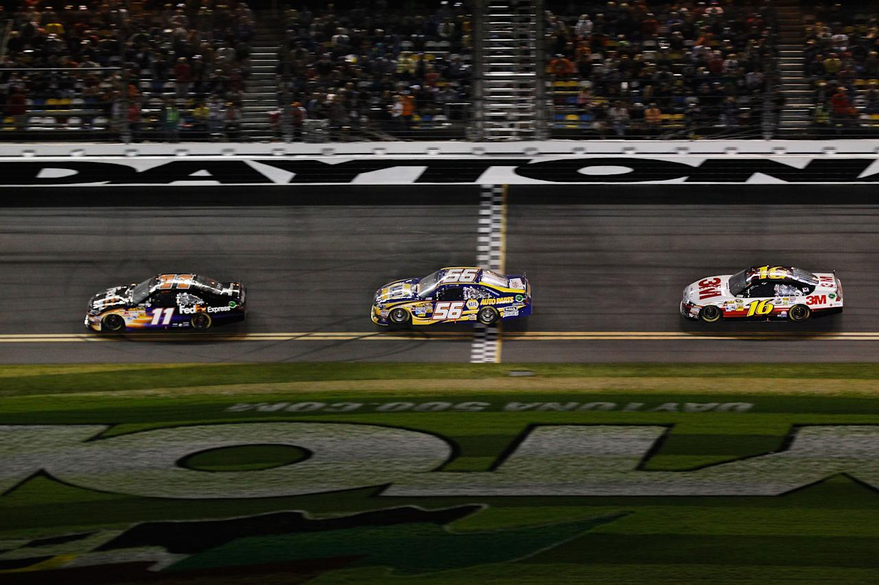DAYTONA BEACH, FL - FEBRUARY 27:  Denny Hamlin, driver of the #11 FedEx Express Toyota, leads Martin Truex Jr., driver of the #56 NAPA Auto Parts Toyota, and Greg Biffle, driver of the #16 3M Ford, during the NASCAR Sprint Cup Series Daytona 500 at Daytona International Speedway on February 27, 2012 in Daytona Beach, Florida.  (Photo by Streeter Lecka/Getty Images)