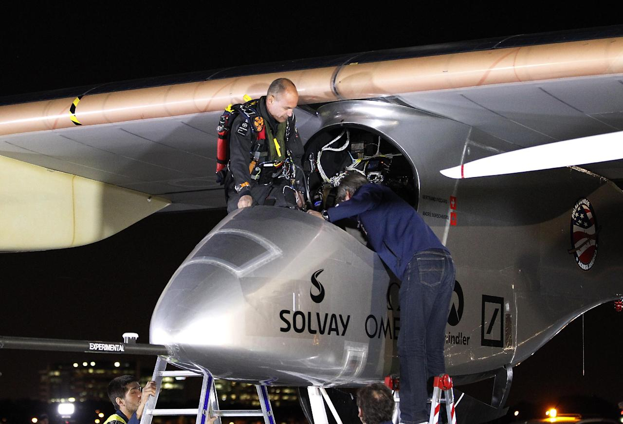 The Solar Impulse pilot Bertrand Piccard, left, enters the cockpit before taking off to embark on a multi-city trip across the United States from Moffett Field NASA Ames Research Center in Mountain View, Calif., Friday, May 3, 2013. Solar Impulse, considered the world's most advanced solar-powered plane, will stop for seven to 10 days at major airports in each city, so the pilots can display and discuss the aircraft with reporters, students, engineers and aviation fans. It plans to reach New York's Kennedy Airport in early July — without using a drop of fuel, its creators said. (AP Photo/Tony Avelar)