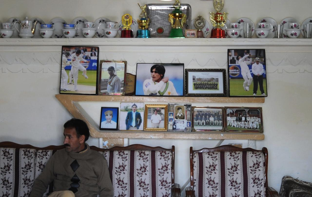 Muhammad Ashraf, brother-in-law of banned Pakistani cricketer Mohmammad Aamer sits in front of photographs of Aamer displayed in a room at the family residence in Changa Bangial village some 73 kilometres east of Islamabad on Febraury 2, 2012. Mohammad Aamer will announce his next move when he returns home later this month after his release from a British prison, his brother told AFP. Aamer was one of three Pakistan players jailed by a judge in London in November 2011 over their roles in a plan to bowl deliberate no-balls during a Test against England at Lord's in August 2010. (AAMIR QURESHI/AFP/Getty Images)