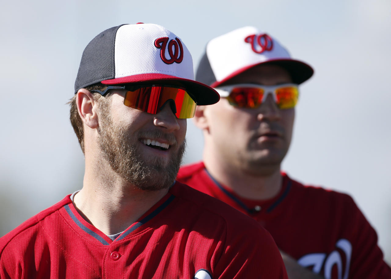 Washington Nationals left fielder Bryce Harper, left, smiles with Ryan Zimmerman during a spring training baseball workout, Thursday, Feb. 20, 2014, in VIera, Fla. (AP Photo/Alex Brandon)