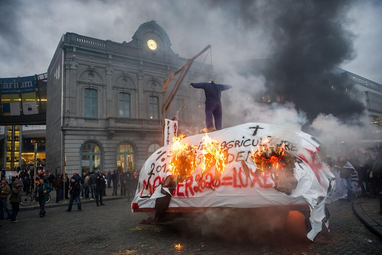 A trailer with hay burns during a European milk farmers demonstration outside the European Parliament in Brussels.