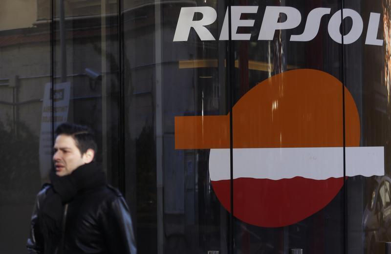 A man walks past a petrol station owned by Spanish oil major Repsol in central Madrid