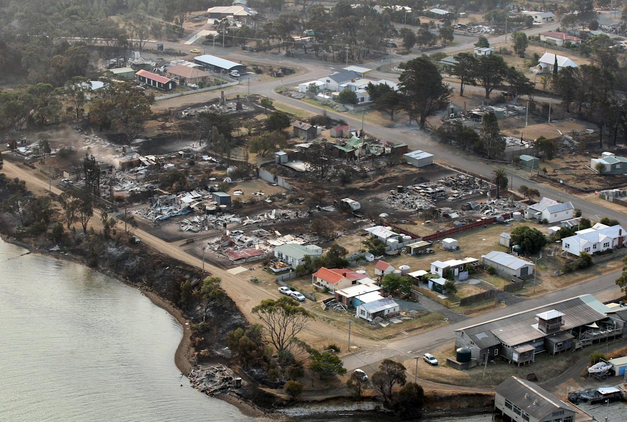 This aerial photo shows a view of Dunalley after a wildfire destroyed around 80 buildings in and around the small town, east of the Tasmanian capital of Hobart, Australia, on Saturday, Jan. 5, 2013. Australian officials battled a series of wildfires amid scorching temperatures across the country on Saturday, with one blaze destroying dozens of homes in the island state of Tasmania. (AP Photo/Chris Kidd, Pool)