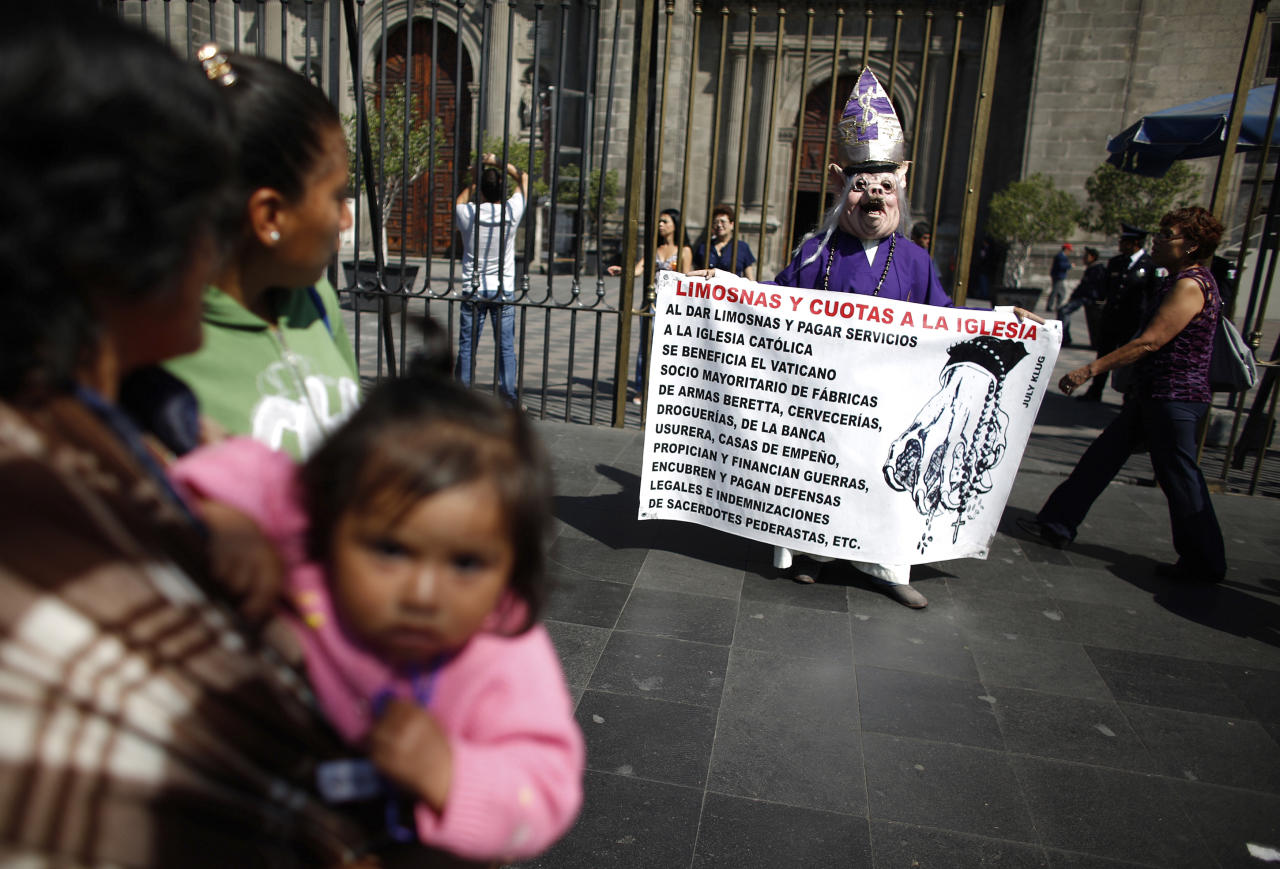 A woman, dressed as a cardinal and wearing a hog mask, holds a banner while yelling slogans against the Catholic clergy outside the Metropolitan Cathedral in Mexico City February 11, 2013. Pope Benedict stunned the Roman Catholic Church including his closest advisers on Monday when he announced he would stand down in the first papal abdication in 700 years, saying he no longer had the mental and physical strength to run the Church through a period of major crisis. REUTERS/Tomas Bravo (MEXICO - Tags: RELIGION POLITICS) - RTR3DNG3