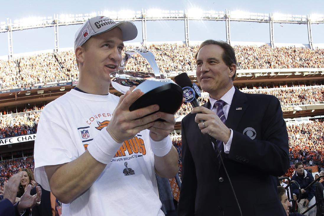 Denver Broncos quarterback Peyton Manning, left, accepts the championship trophy after the AFC Championship NFL playoff football game in Denver, Sunday, Jan. 19, 2014. The Broncos defeated the Patriots 26-16 to advance to the Super Bowl. (AP Photo/Charlie Riedel)