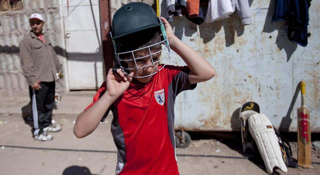 Caacupe cricket team Maxi Rubin puts on his helmet during a training session at the Villa 21-24 slum in Buenos Aires, Argentina, Saturday, March 22, 2014. The International Cricket Council has recognized the team, formed from the children of the Villa 21-24 shantytown, honoring them as a global example for expanding the sport, which in certain countries, like India, is widely played, but in many parts of the world restricted to elite sectors of society. Introducing cricket in the slum began in 2009 as an idea to transform the game into a social integration mechanism, before that it rarely breached the gates of the country's upscale private schools. (AP Photo/Natacha Pisarenko)