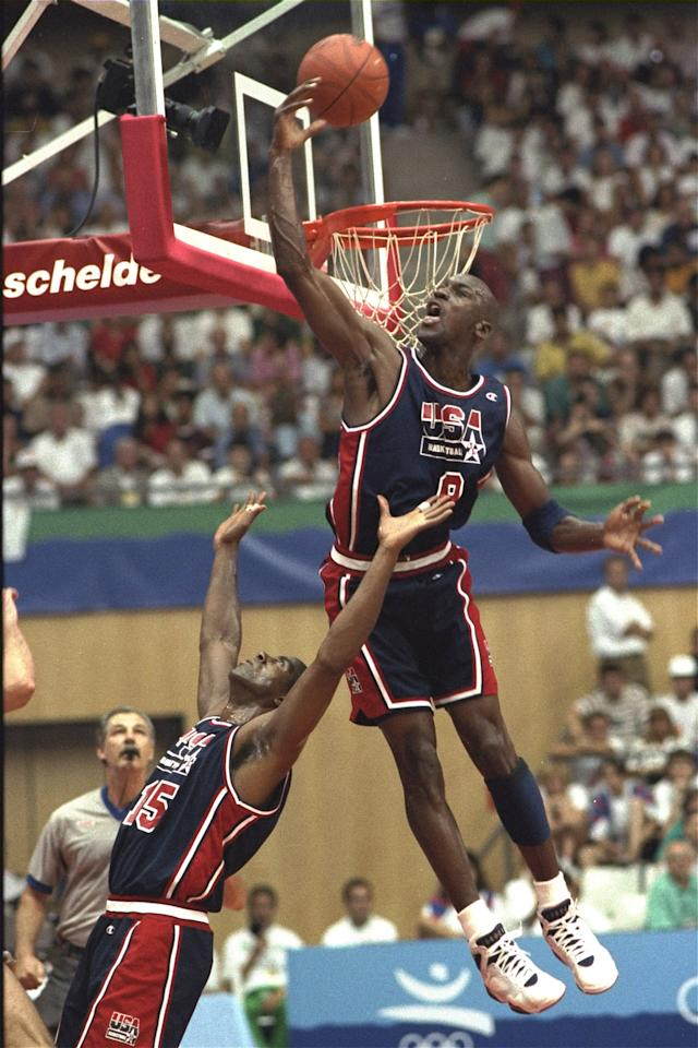 USA's Michael Jordan sails high above teammate Magic Johnson knocking away a shot during the first half of their preliminary round basketball game with Croatia at the Summer Olympics in Barcelona Monday, July 27, 1992. (AP Photo/Susan Ragan)