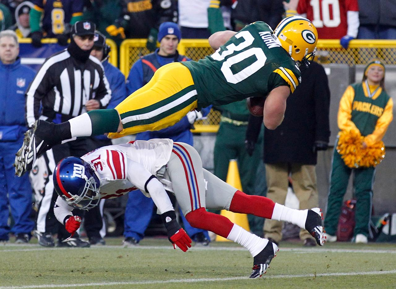 Green Bay Packers fullback John Kuhn (30) dives over New York Giants cornerback Aaron Ross during an 8-yard touchdown reception in the first the first half of an NFL divisional playoff football game Sunday, Jan. 15, 2012, in Green Bay, Wis.(AP Photo/Jeffrey Phelps)