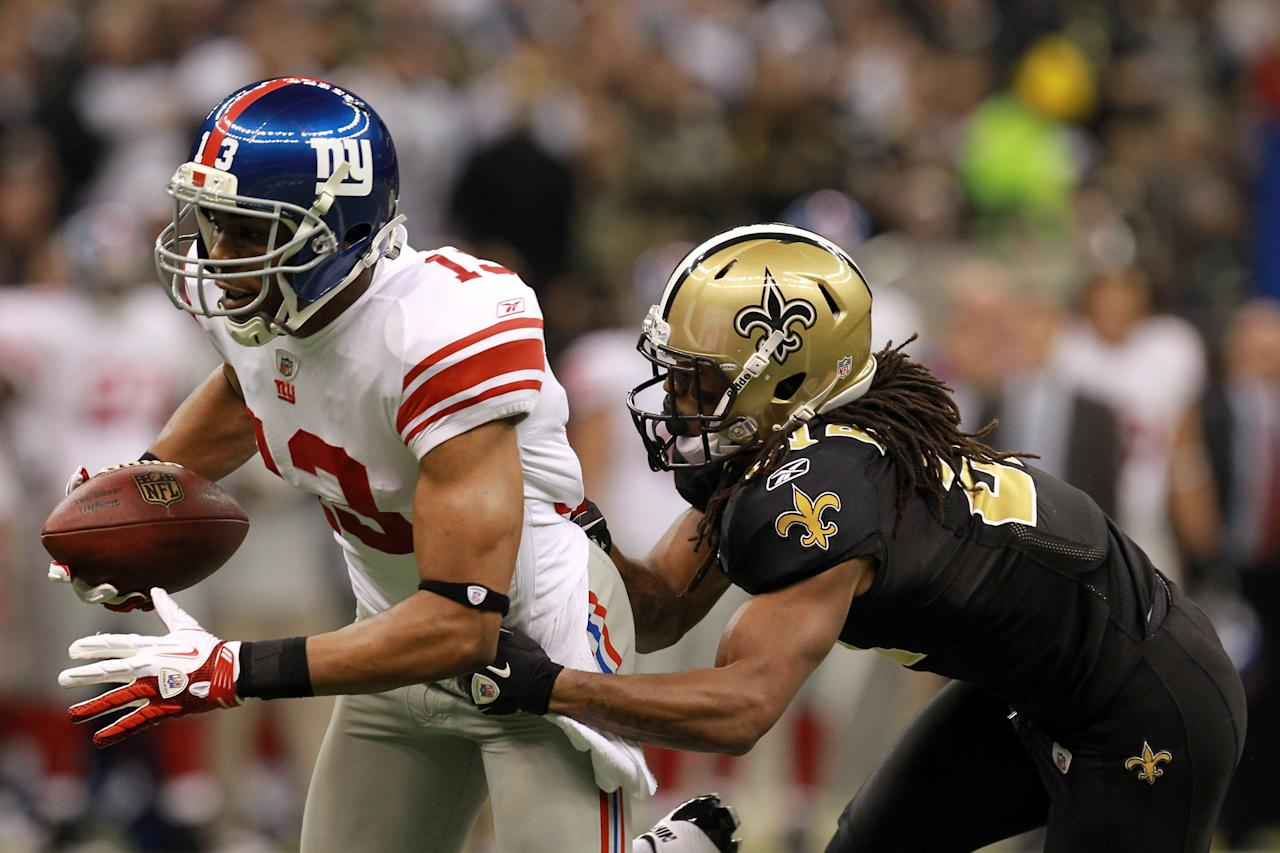 NEW ORLEANS, LA - NOVEMBER 28:  Wide receiver  Ramses Barden #13 of the New York Giants runs after a catch for a 26-yard gain as he is tackled by cornerback Patrick Robinson #21 of the New Orleans Saints in the first quarter at Mercedes-Benz Superdome on November 28, 2011 in New Orleans, Louisiana.  (Photo by Ronald Martinez/Getty Images)