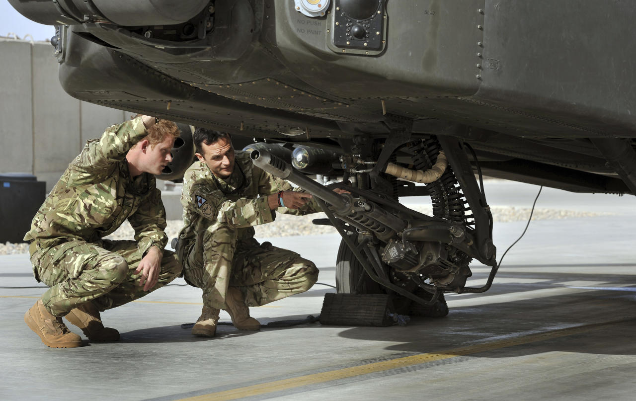 Prince Harry examines the 30mm cannon of an Apache helicopter with an unidentified member of his squadron at Camp Bastion in Afghanistan September 7, 2012. REUTERS/John Stillwell/Pool