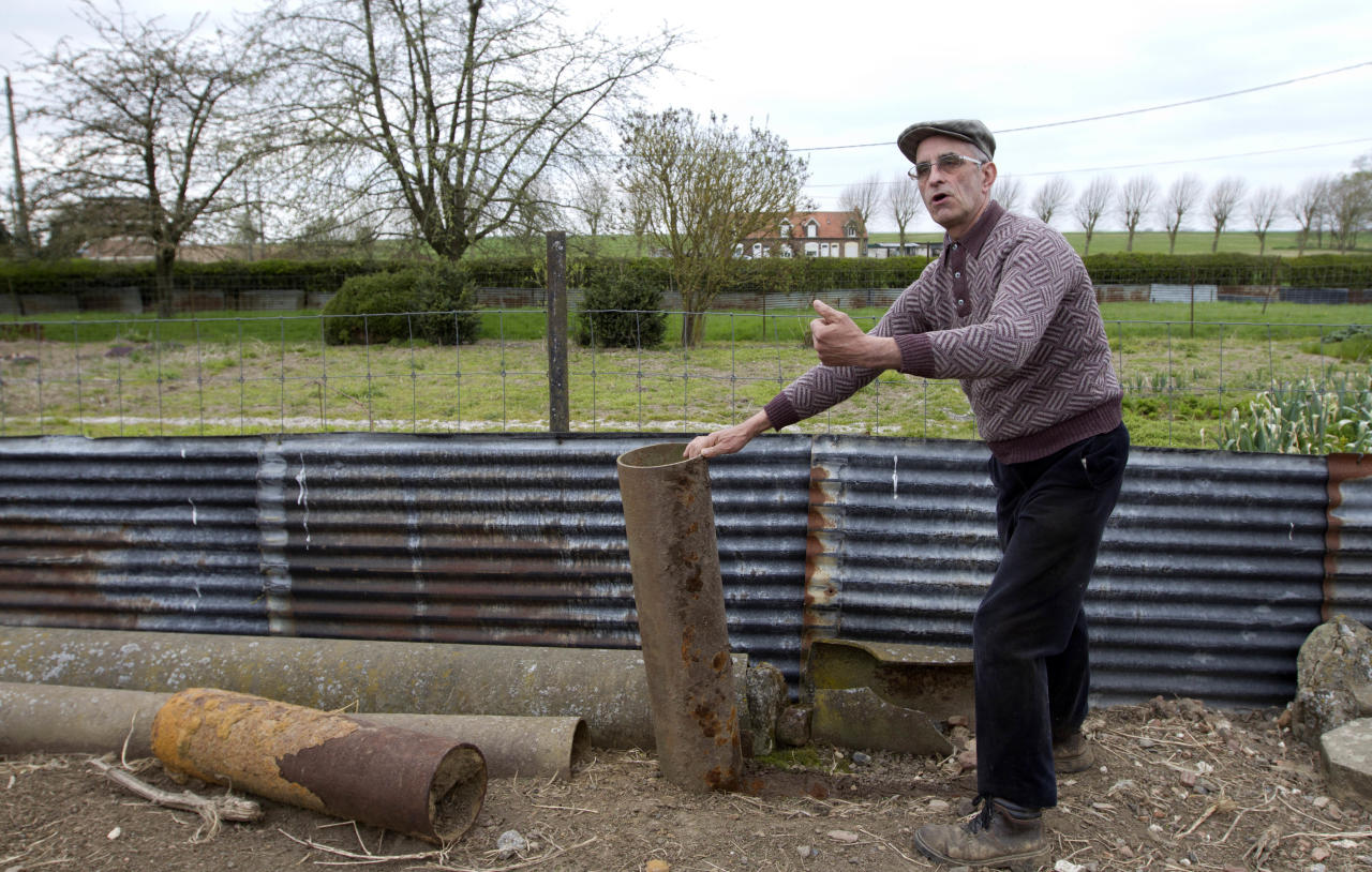 Farmer Didier Guerle shows the shell of a World War One gas bomb found in a field near the site of where he also located the bodies of two British World War One soldiers in Bullecourt, France on Monday April 22, 2013. Almost 100 years after they were killed in action, Lieutenant John Harold Pritchard and Private Christopher Douglas Elphick will be re-interred with full military honors in the H.A.C Cemetery at Ecoust-St. Mein, France, on Tuesday, April 23, 2013. (AP Photo/Virginia Mayo)