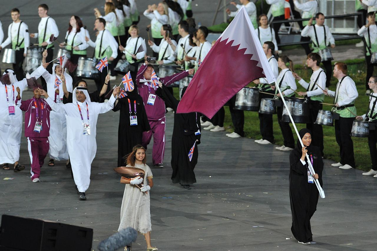 LONDON, ENGLAND - JULY 27:  Bahya Mansour Al Hamad of the Qatar Olympic shooting team carries her country's flag during the Opening Ceremony of the London 2012 Olympic Games at the Olympic Stadium on July 27, 2012 in London, England.  (Photo by Pascal Le Segretain/Getty Images)