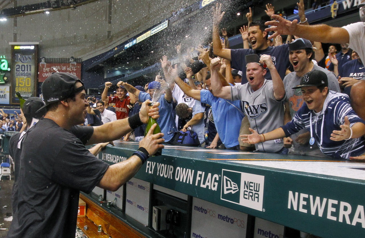 Tampa Bay Rays' Evan Longoria, left, celebrates sprays fans early Thursday, Sept. 29, 2011, after the Rays clinched the AL wild card with an 8-7 win over the New York Yankees in a baseball game in St. Petersburg, Fla. (AP Photo/Mike Carlson)