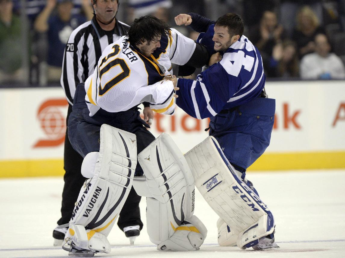 Buffalo Sabres goalie Ryan Miller fights with Toronto Maple Leafs goalie Jonathan Bernier during the third period of an NHL hockey preseason game in Toronto, Sunday Sept. 22, 2013. (AP Photo/The Canadian Press, Frank Gunn)