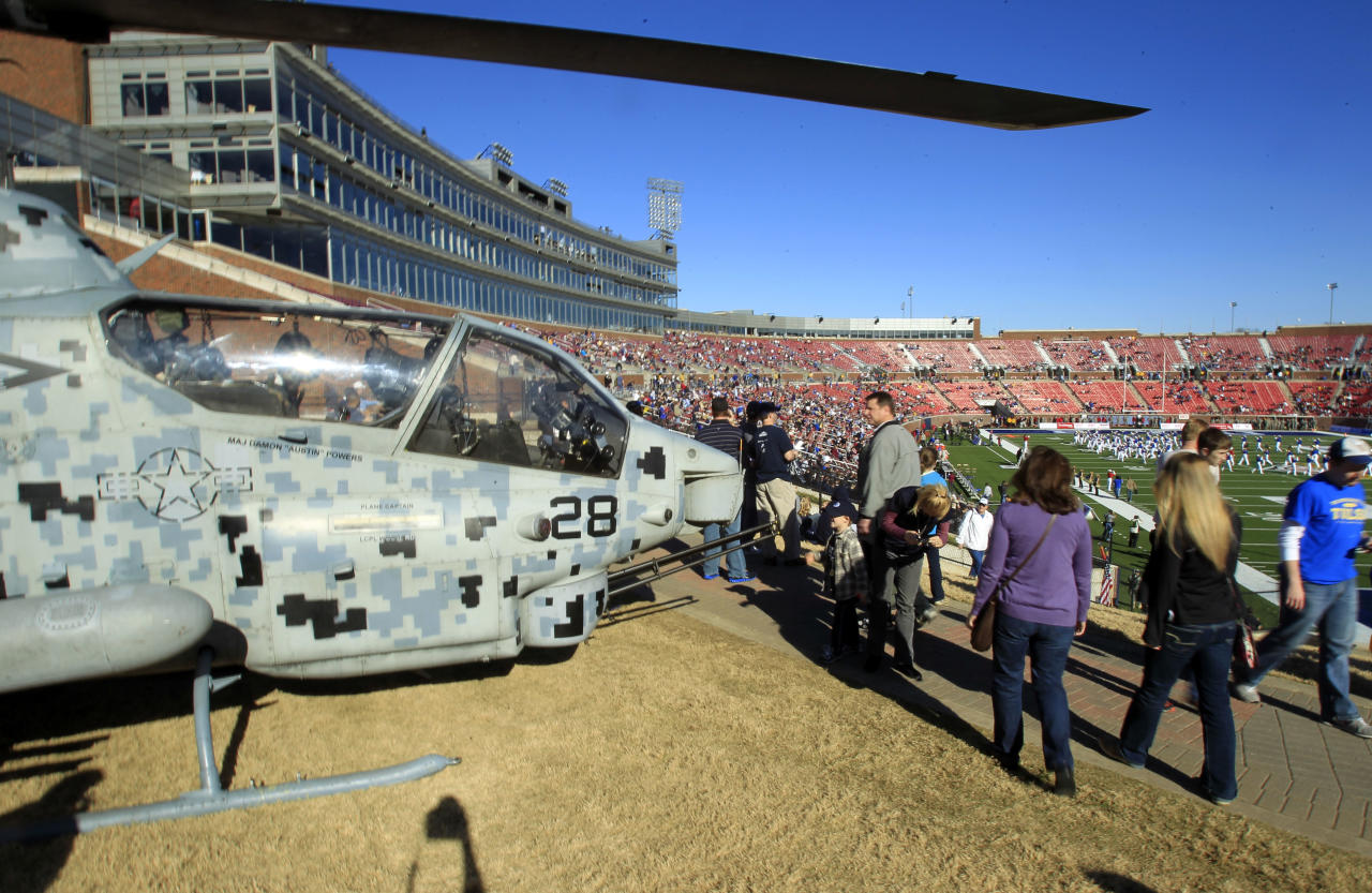 Fans walk past a parked Cobra attack helicopter while heading to their seats before the start of the Armed Forces Bowl college football game between BYU and Tulsa on Friday, Dec. 30, 2011, in Dallas. (AP Photo/John F. Rhodes)