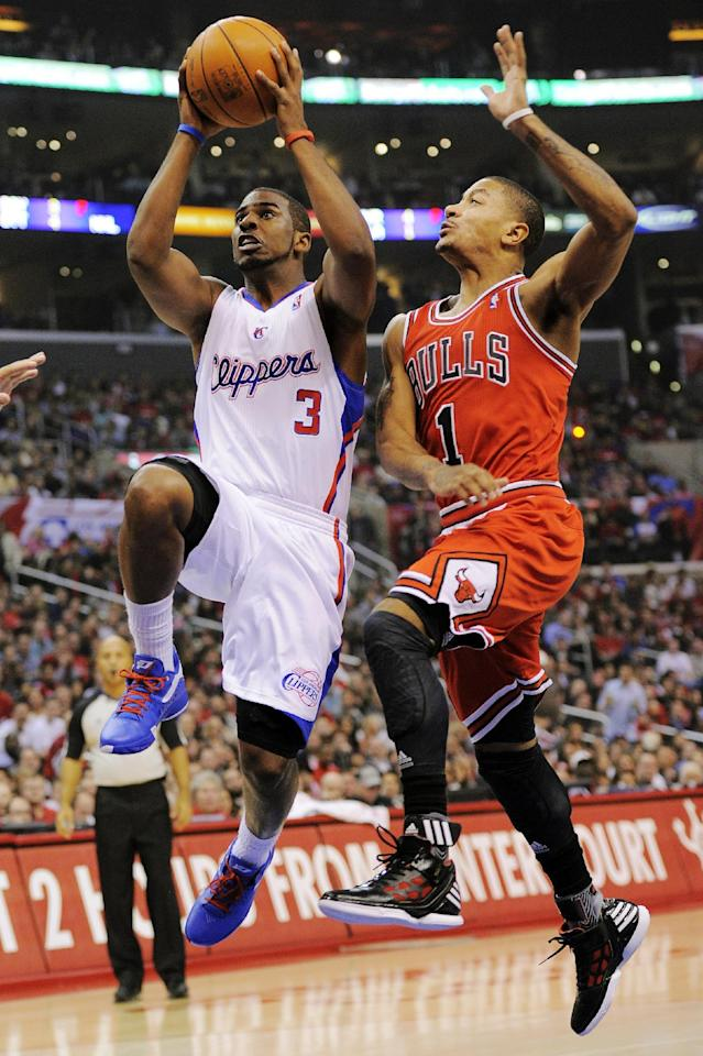 Los Angeles Clippers guard Chris Paul, left, goes up for a shot as Chicago Bulls guard Derrick Rose defends during the first half of their NBA basketball game, Friday, Dec. 30, 2011, in Los Angeles. (AP Photo/Mark J. Terrill)