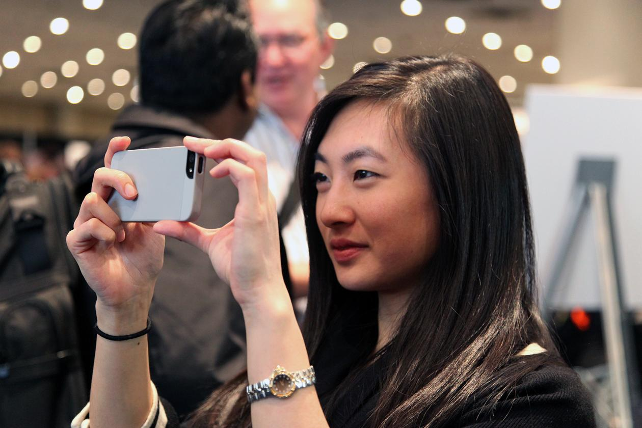 Mona Zhang, of New York City, snapping a photo with her cell phone in front of one of 3D systems demonstrations.