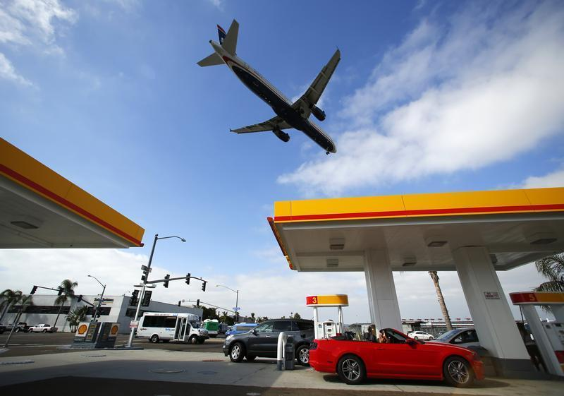 Consumers purchase gasoline at a gas station as a plane approaches to land at the airport in San Diego