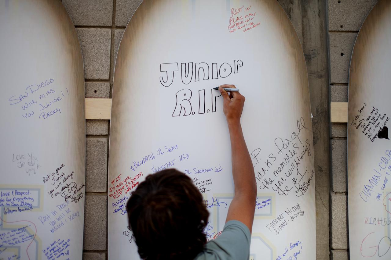 SAN DIEGO, CA - MAY 11: A supporter signs a surfboards  as he pays tribute to former NFL star Junior Seau during a public memorial at Qualcomm Stadium May 11, 2012 in San Diego, California. Seau, who played for various NFL teams including the San Diego Chargers, Miami Dolphins and New England Patriots, was found dead in his home on May 2, an apparent suicide.  (Photo by Sandy Huffaker/Getty Images)