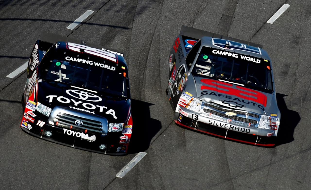 MARTINSVILLE, VA - OCTOBER 29:  Denny Hamlin, driver of the #18 Toyota/Traxxas Toyota, races Johnny Sauter, driver of the #13 SafeAuto Insurance Co./Curb Records Chevrolet, during the NASCAR Camping World Truck Series Kroger 200 at Martinsville Speedway on October 29, 2011 in Martinsville, Virginia.  (Photo by Jeff Zelevansky/Getty Images for NASCAR)