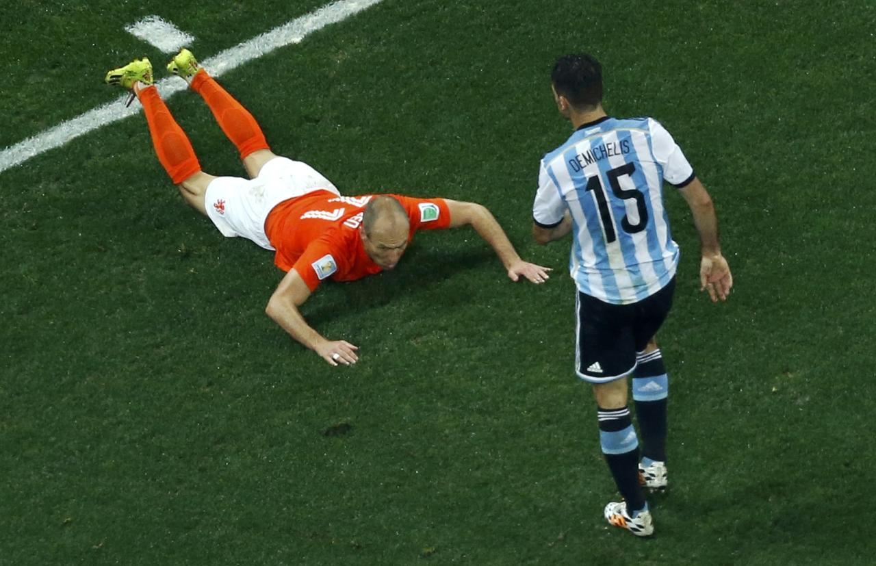 Arjen Robben of the Netherlands falls in front of Argentina's Martin Demichelis (R) during their 2014 World Cup semi-finals at the Corinthians arena in Sao Paulo July 9, 2014. REUTERS/Fabrizio Bensch (BRAZIL - Tags: SOCCER SPORT WORLD CUP)