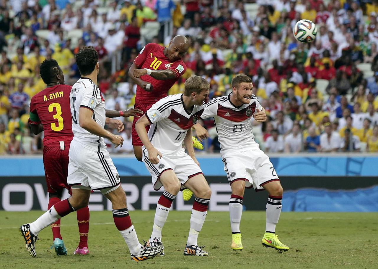 Ghana's Andre Ayew heads the ball over Germany's Per Mertesacker, center, and Germany's Shkodran Mustafi, right, to score his sides' first goal during the group G World Cup soccer match between Germany and Ghana at the Arena Castelao in Fortaleza, Brazil, Saturday, June 21, 2014. (AP Photo/Marcio Jose Sanchez)