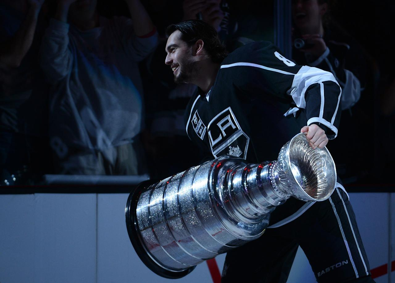 LOS ANGELES, CA - JANUARY 19:  Drew Doughty #8 of the Los Angeles Kings carries the Stanley Cup during a ceremony before the NHL season opening game against the Chicago Blackhawks at Staples Center on January 19, 2013 in Los Angeles, California.  (Photo by Harry How/Getty Images)