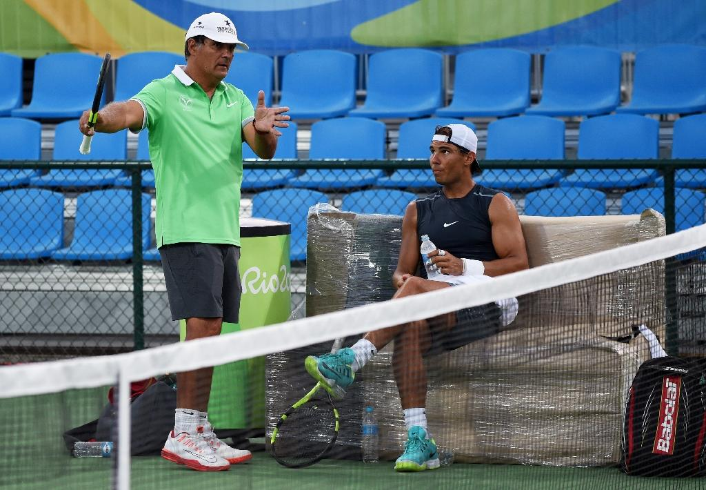 Rafael Nadal of Spain (R) listening to his coach and uncle Toni Nadal during a tennis practice session at the Olympic park in Rio de Janeiro ahead of the 2016 Rio Olympic Games (AFP Photo/ROBERTO SCHMIDT)