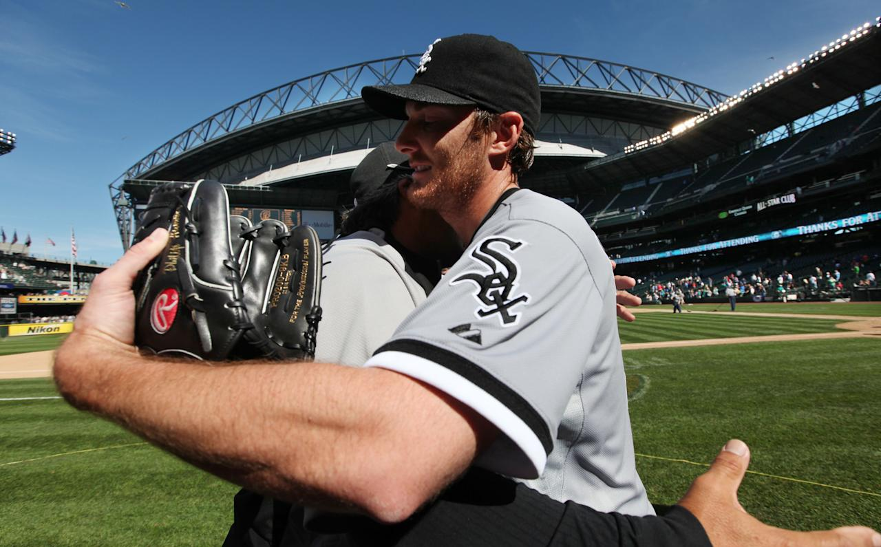 Chicago White Sox starting pitcher Phil Humber, right, is hugged after pitching a perfect baseball game against the Seattle Mariners, Saturday, April 21, 2012, in Seattle. The White Sox won 4-0. (AP Photo/Elaine Thompson)