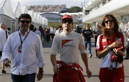 Ferrari Formula One driver Alonso of Spain walks in the paddock with his agent Garcia Abad and his press officer Vallorosi after the qualifying session of the Japanese F1 Grand Prix at the Suzuka circuit