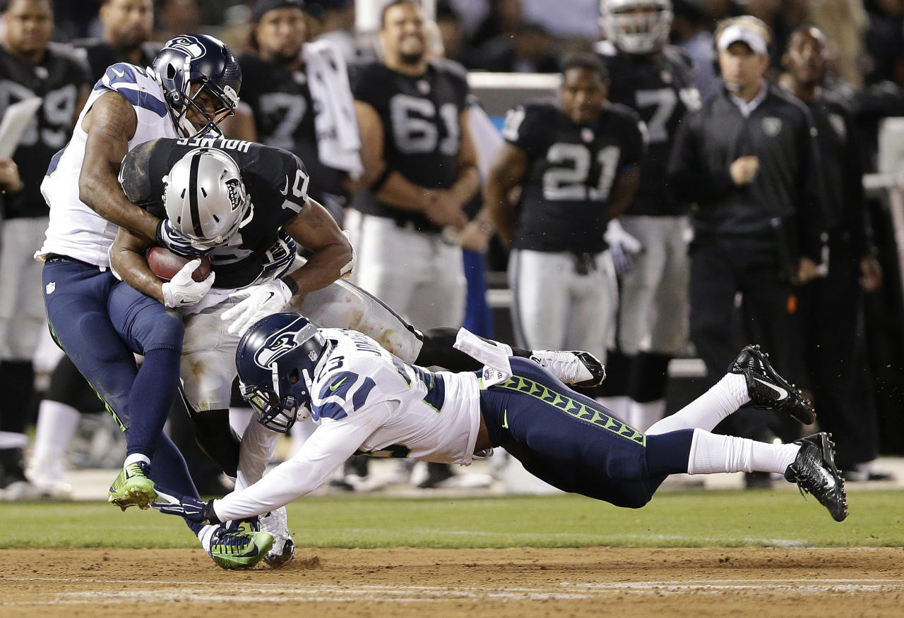 Oakland Raiders wide receiver Andre Holmes (18) is tackled by Seattle Seahawks defensive back DeShawn Shead (35) and strong safety Jeron Johnson during the second quarter of an NFL preseason football game in Oakland, Calif., Thursday, Aug. 28, 2014. (AP Photo/Marcio Jose Sanchez)