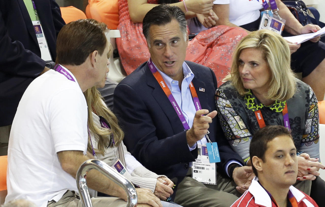 United States Republican presidential candidate Mitt Romney, center, and his wife Ann, right, talk to unidentified spectators on the opening day of swimming competitions at the Aquatics Centre in the Olympic Park during the 2012 Summer Olympics in London, Saturday, July 28, 2012. (AP Photo/Lee Jin-man)