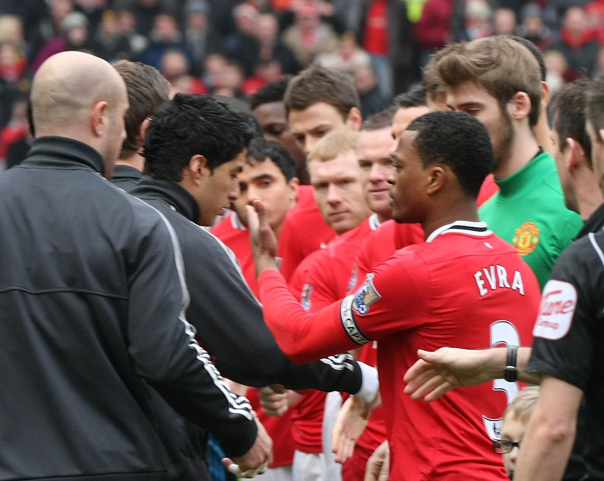 MANCHESTER, ENGLAND - FEBRUARY 11:  Luis Suarez of Liverpool refuses to shake the hand of Patrice Evra of Manchester United ahead of the Barclays Premier League match between Manchester United and Liverpool at Old Trafford on February 11, 2012 in Manchester, England.  (Photo by Matthew Peters/Man Utd via Getty Images)
