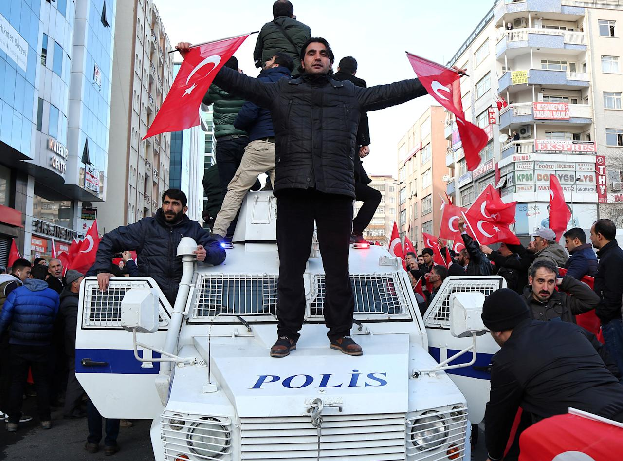 A demonstrator waves Turkish flags on top of a police vehicle during a protest against Saturday's blast targetting military personnel in Kayseri, in the southeastern city of Diyarbakir, Turkey, December 18, 2016. REUTERS/Sertac Kayar     TPX IMAGES OF THE DAY