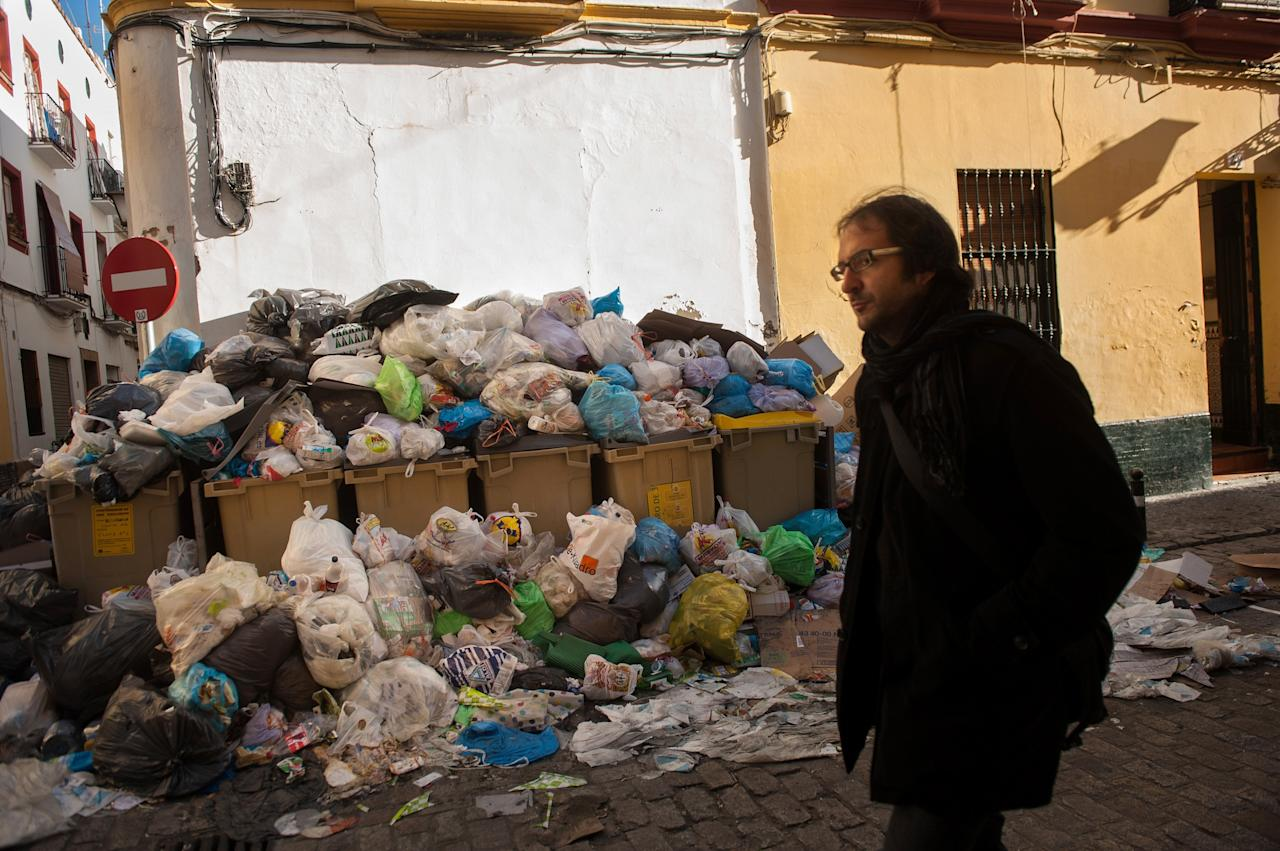 SEVILLE, SPAIN - FEBRUARY 06:  A pedestrian passes a pile of garbage during the 10th day of the Seville waste disposal strike on February 6, 2013 in Seville, Spain. Workers are striking over demands they take a 5% pay cut and extend their working week to 37.5 hours.  (Photo by Denis Doyle/Getty Images)
