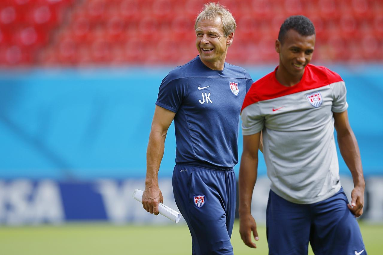 The U.S. national soccer team head coach Juergen Klinsmann (L) smiles as his team, including midfielder Julian Green, stretch during a training session at the Pernambuco arena in Recife June 25, 2014. REUTERS/Brian Snyder (BRAZIL - Tags: SOCCER SPORT WORLD CUP)