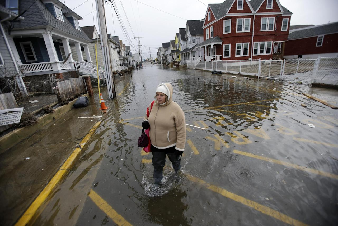 Carol Marelli walks down her flooded street Thursday, March 7, 2013, in Sea Bright, N.J., after an overnight storm. Flooding remained a problem in this and other shore towns. Water on roadways was also forcing closures in towns including Monmouth Beach, Absecon, Aberdeen, Egg Harbor Township and Wildwood. A coastal flood warning remains in effect until 9 a.m. Friday, but forecasters were not expecting Thursday's wind to be as strong as Wednesday, when gusts exceeding 60 mph were recorded in many places along the ocean. (AP Photo/Mel Evans)