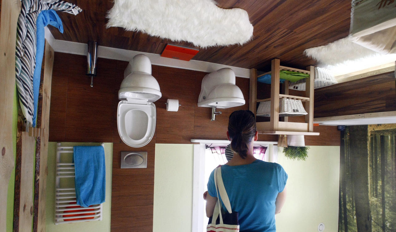 A woman stands inside the bathroom of a house, which was built upside down by Polish architects Irek Glowacki and Marek Rozhanski, in the western Austrian village of Terfens May 5, 2012. The project is meant to serve as a new tourist attraction in the area, and is now open for public viewing. Picture taken May 5, 2012. REUTERS/Dominic Ebenbichler (AUSTRIA - Tags: SOCIETY TRAVEL) - RTR31O4K