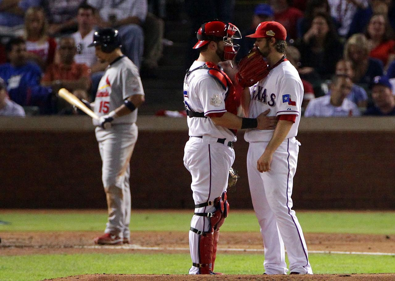ARLINGTON, TX - OCTOBER 24:  C.J. Wilson #36 and Mike Napoli #25 of the Texas Rangers talk on the mound during Game Five of the MLB World Series against the St. Louis Cardinals at Rangers Ballpark in Arlington on October 24, 2011 in Arlington, Texas.  (Photo by Doug Pensinger/Getty Images)