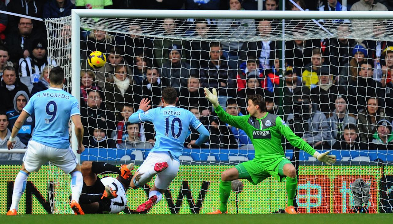 NEWCASTLE UPON TYNE, ENGLAND - JANUARY 12: Manchester City striker Edin Dzeko (c) scores the opening goal past Tim Krul during the Barclays Premier League match between Newcastle United and Manchestre City at St James' Park on January 12, 2014 in Newcastle upon Tyne, England. (Photo by Stu Forster/Getty Images)