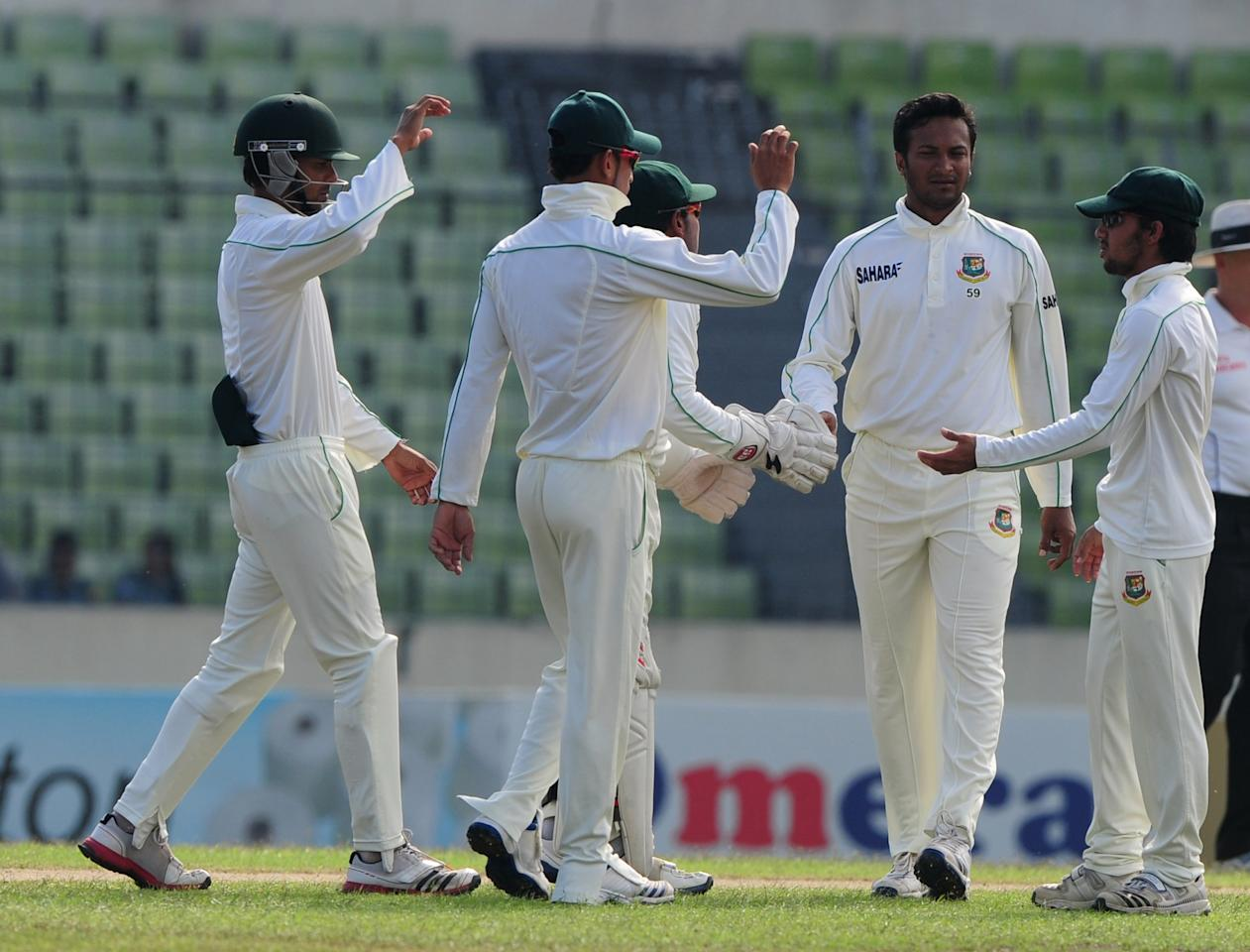 Bangladesh cricketer  Shakib Al Hasan (2nd R) celebrates with his teammates after the dismissal of the unseen New Zealand batsman Ish Sodhi during the fourth day of the second cricket Test match between Bangladesh and New Zealand at the Sher-e Bangla National Stadium in Dhaka on October 24, 2013. AFP PHOTO/ Munir uz ZAMAN        (Photo credit should read MUNIR UZ ZAMAN/AFP/Getty Images)