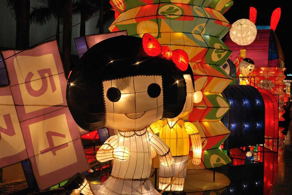 A little girl with a pretty bow in her hair glowing in white is first to greet me. She stands amid a row of lanterns, some towering over me.