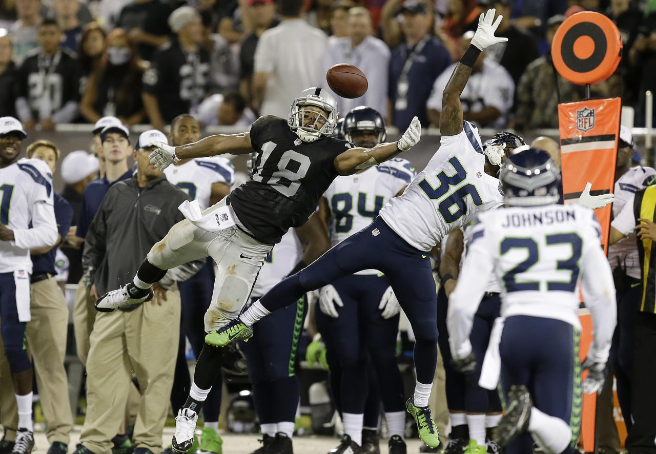 Oakland Raiders wide receiver Andre Holmes (18) reaches but can't make a catch as he is defended by Seattle Seahawks defensive back Akeem Auguste (36) during the first half of an NFL preseason football game in Oakland, Calif., Thursday, Aug. 28, 2014. (AP Photo/Ben Margot)