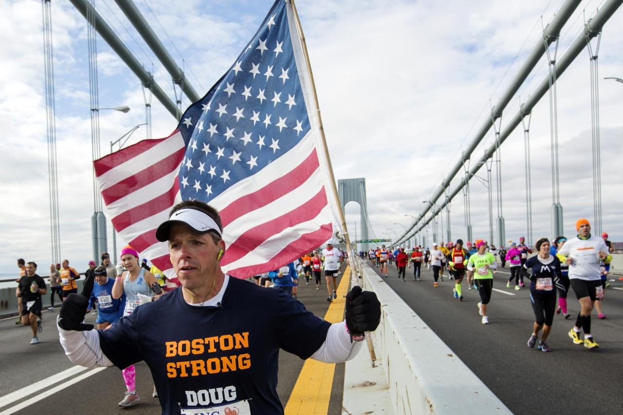 "A runner carrying the U.S. flag and wearing a t-shirt that says ""Boston Strong"" crosses the Verrazano-Narrows Bridge during the New York City Marathon in New York, November 3, 2013. REUTERS/Lucas Jackson (UNITED STATES - Tags: SPORT ATHLETICS)"