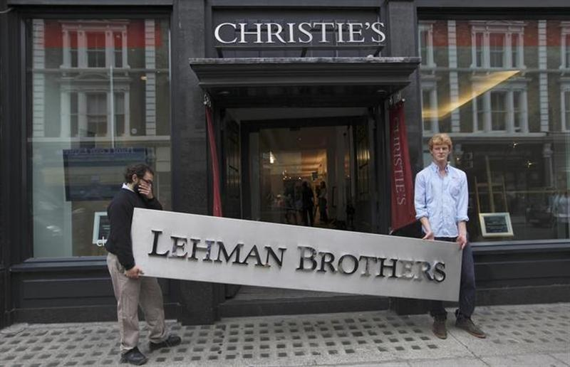 Christie's employees pose for a photograph with a Lehman Brothers sign at Christie's in central London September 24, 2010.