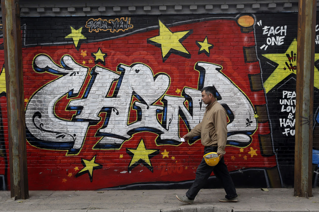 A construction worker passes by a mural at the 798 Art District.