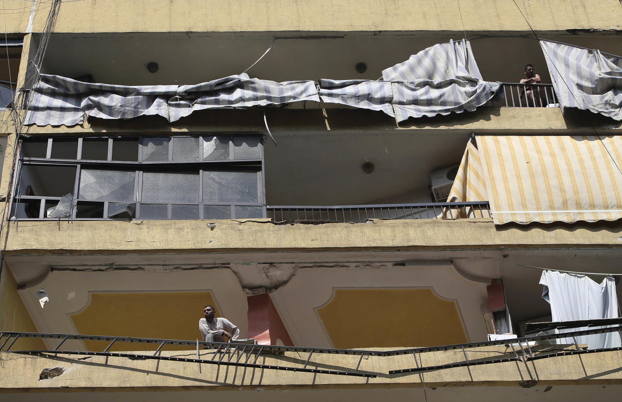 Lebanese citizens stand on their destroyed balconies at the site of a car bomb explosion in southern Beirut, Lebanon, Friday, Aug. 16, 2013. A powerful car bomb tore through a bustling south Beirut neighborhood that is a stronghold of Hezbollah on Thursday, killing at least 18 and trapping dozens of others in an inferno of burning cars and buildings in the bloodiest attack yet on Lebanese civilians linked to Syria's civil war. (AP Photo/Hussein Malla)